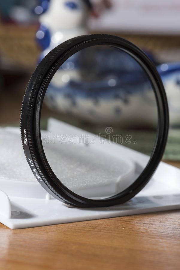 Polarizing CPL filter for the lens on the table in an open box. Polarizing, CPL filter for lens and lens cap on the desktop stock image