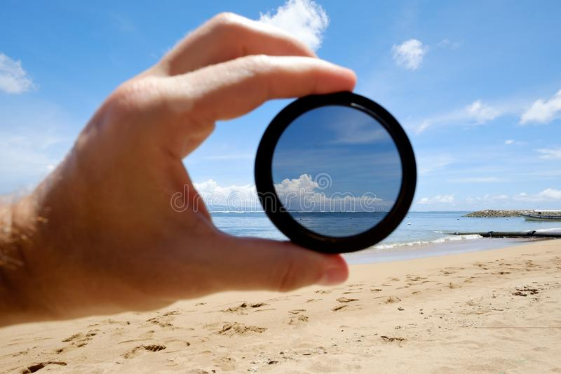 Polarizing filter hold against the beach giving clarity. Optics tool for lens in photography royalty free stock photos
