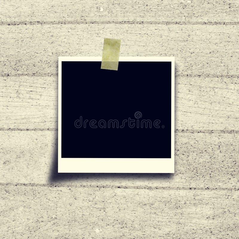 Polaroïd noir de cadre de photo sur le panneau de liège photographie stock