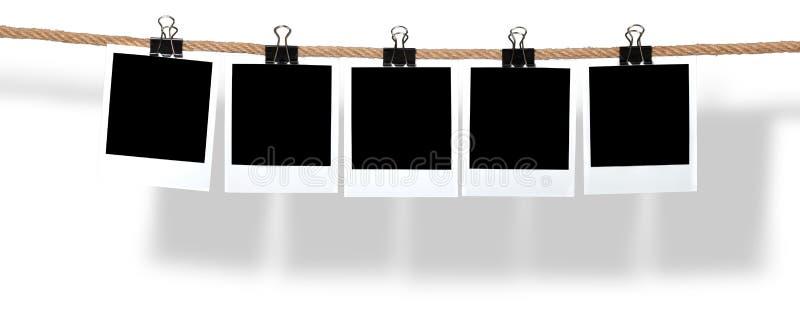 Polaroïds vides pendant d'une corde image stock