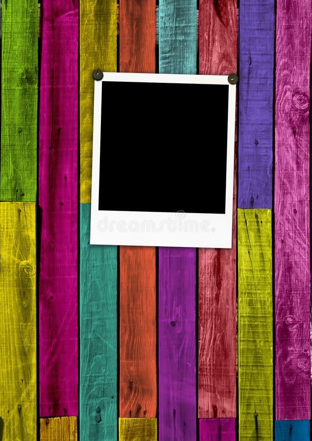 Polaroid in bianco su priorità bassa di legno variopinta fotografia stock