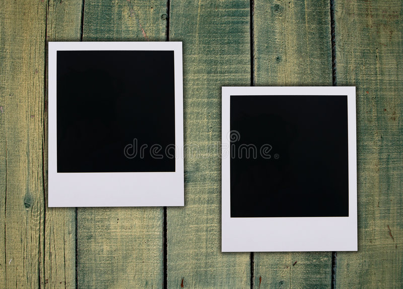 Polaroid blanks. Old Polaroid film blanks on a green stained wooden fence stock photography