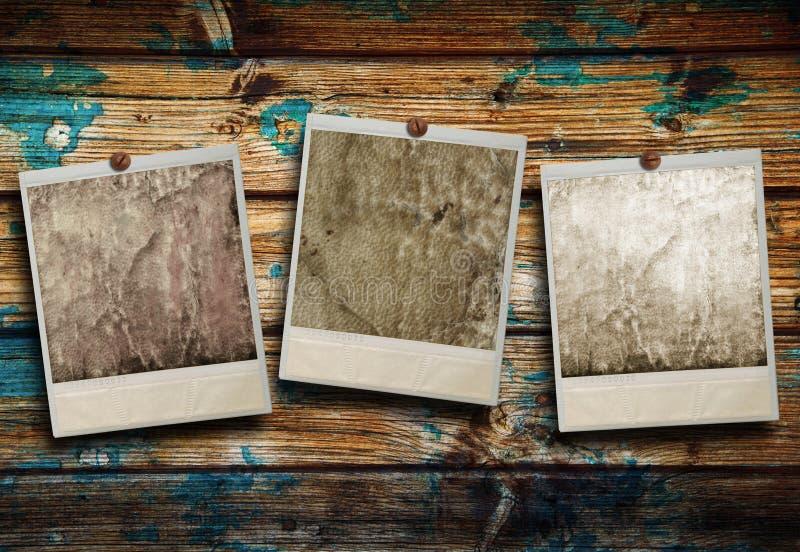 Polaroid drei, das am hölzernen Hintergrund hängt lizenzfreie stockfotos