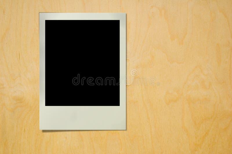 Polaroid na textura de madeira foto de stock