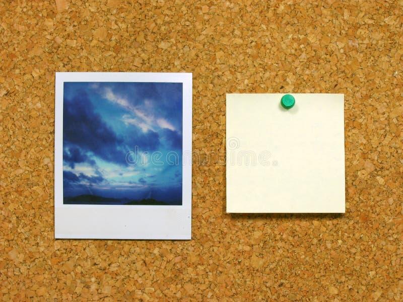 Polaroid & post-it on corkboard stock photography