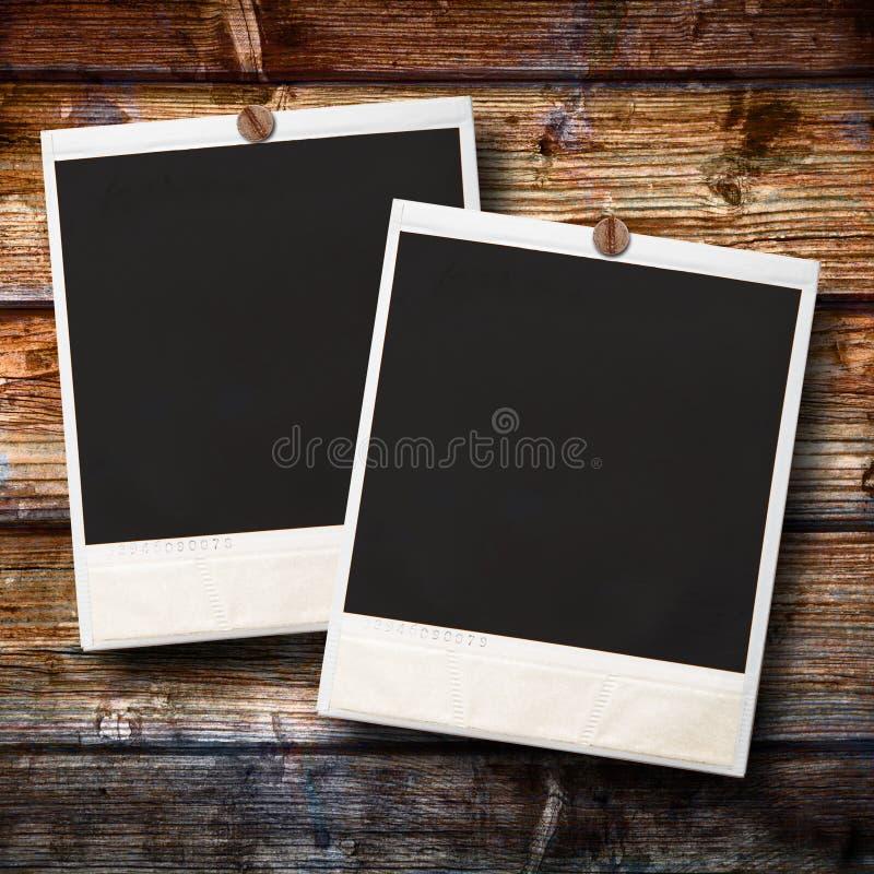 Polaroid zwei, das am hölzernen Hintergrund hängt lizenzfreie stockfotos