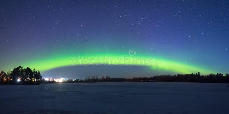 Polart norrsken för nordliga ljus på natten i den stjärnklara himlen ovanför sjön med ön och konturn av träden förbi arkivbilder