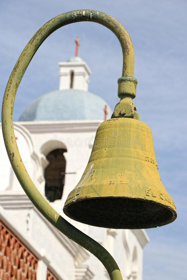 Pole of an antique bell frames the steeple of an old church stock images