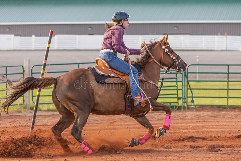 Pole Bender. Young woman competing in a pole bending equestrian competition stock photos