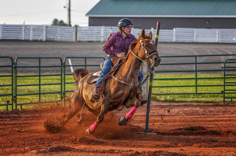 Pole Bender. Young woman competing in a pole bending equestrian competition royalty free stock photo