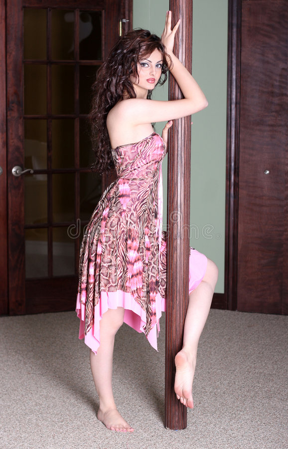 Pole dance. Model posing using a pole dance royalty free stock photography