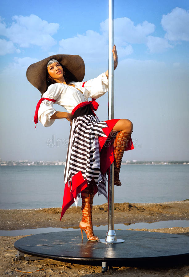 Pole dance girl in dress and hat.