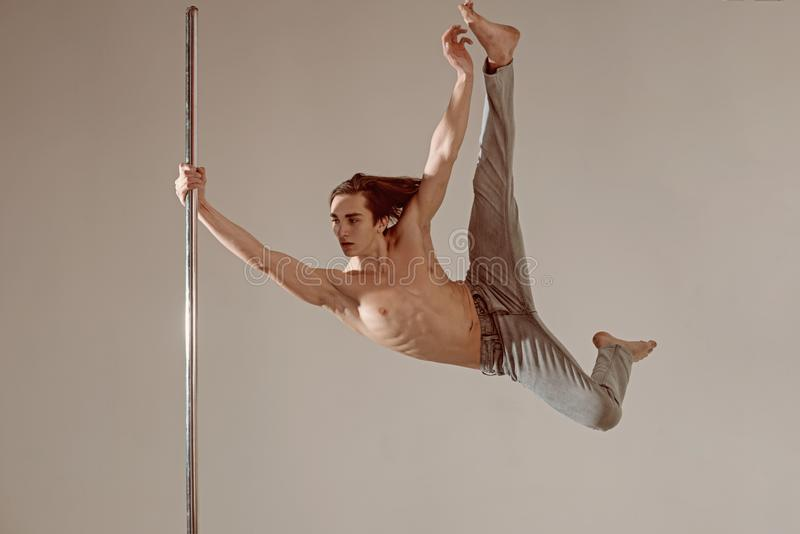 Pole Dance Male Athlete, aesha split on grey background.  stock photo