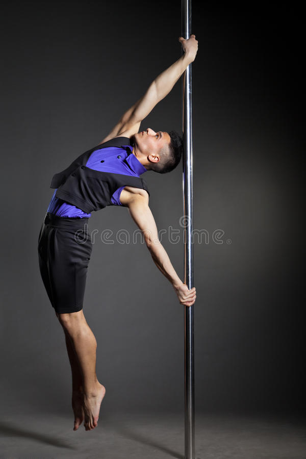 Pole dance man over black background with flashes. Young strong pole dance man over black background with flashes royalty free stock image