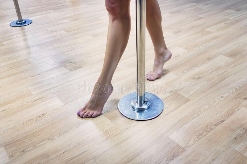Pole dancer's bare legs performing on floor in dance hall. Close up of female poledancer feet on dancefloor. Warming up in stock photography