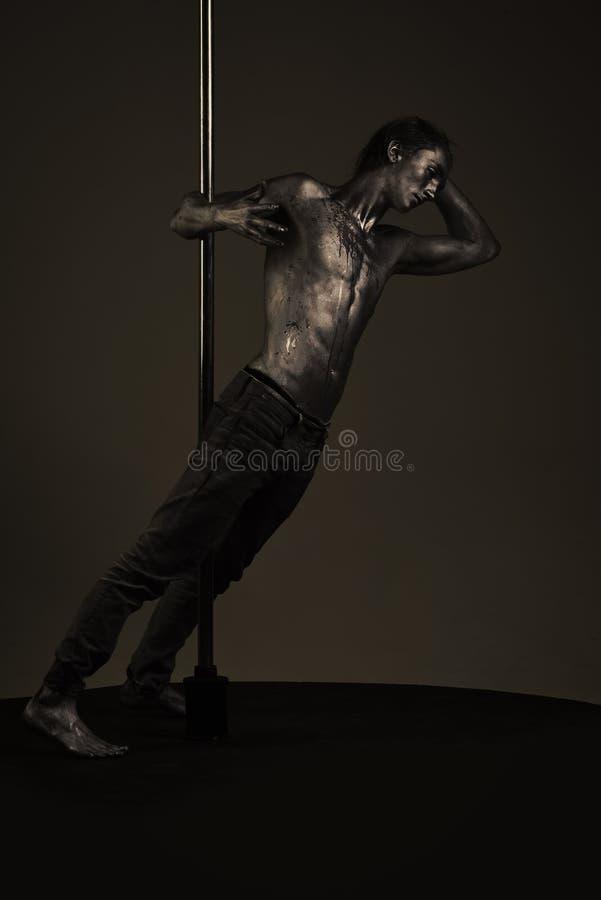 Pole dans Man med den näcka torson som täckas med skimrande målarfärg, mörk bakgrund arkivfoto