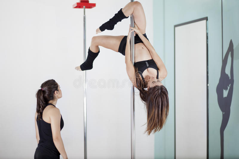 Pole fitness instructor supervising. Cute young pole fitness instructor coaching and supervising a student while doing a pose royalty free stock photography