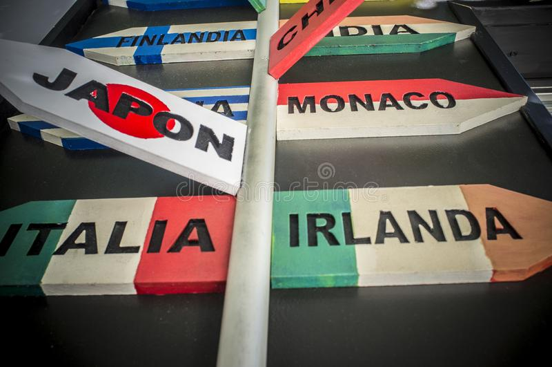 Guidepost with multiple destination countries of the world on arrows sticks in Spanish stock photography