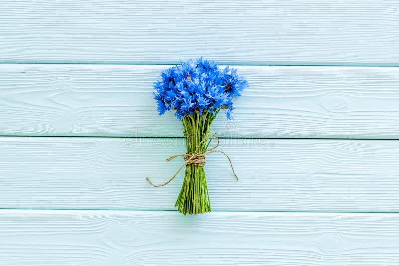 Pole kwiatów projekt z bukietem błękitni cornflowers na mennicy zieleni tła odgórnego widoku drewnianej przestrzeni dla teksta zdjęcie stock
