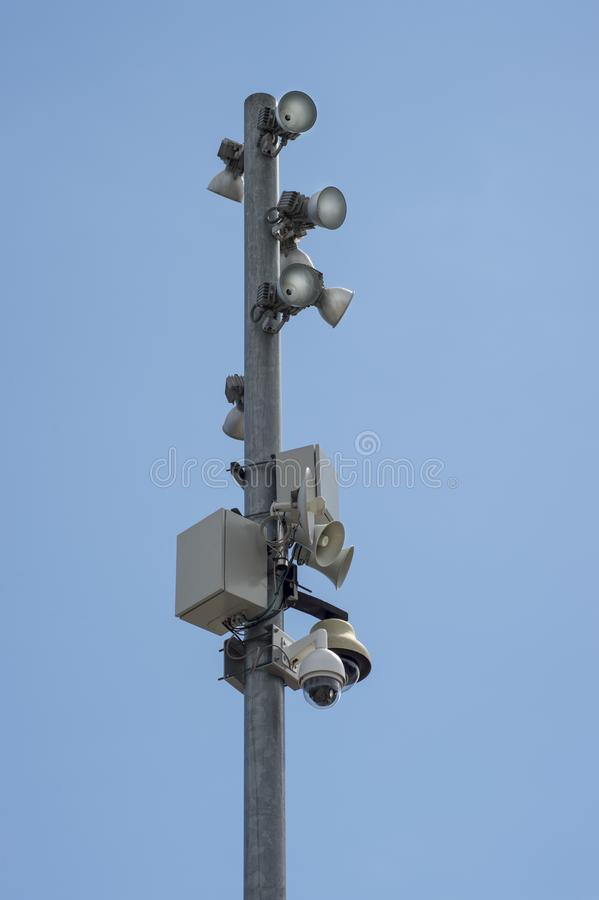 Pole with lights on the antennas. Iron gray post on which are attached lights , video cameras and equipment. In the background, blue clear sky royalty free stock photography