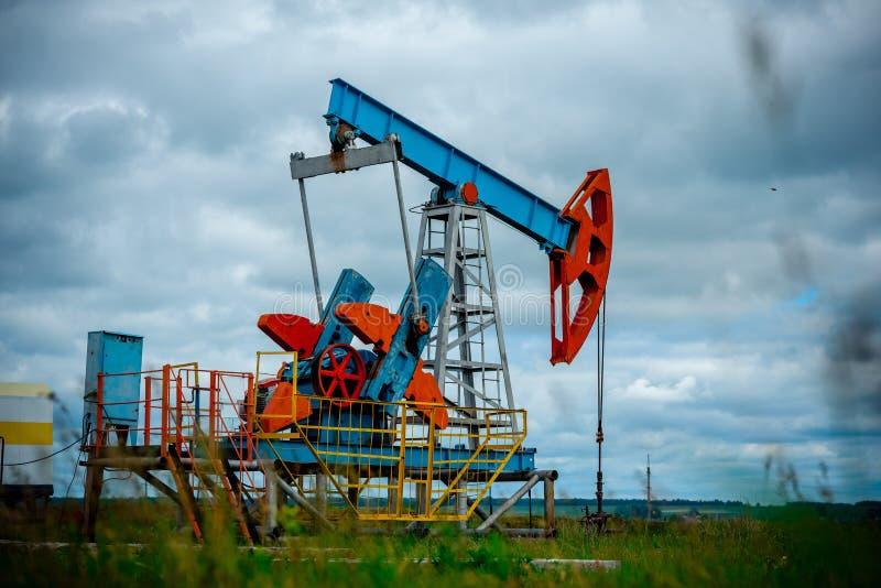 Pole naftowe z pompową dźwigarką, profilującą na niebieskim niebie z białymi chmurami na słonecznym dniu w wiośnie, zdjęcie stock