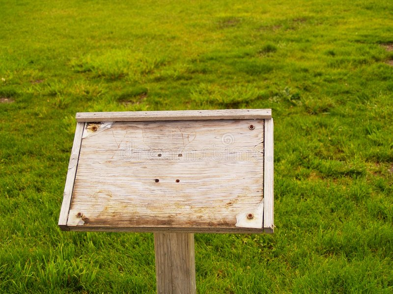 pole trawiasty noszących znak drewna obraz stock