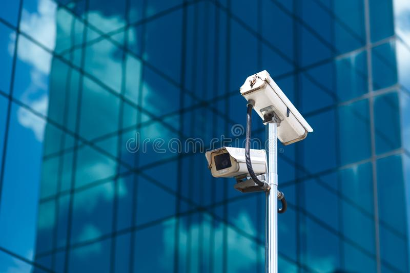 Pole with two white video surveillance cameras at big office glass building background.  royalty free stock images