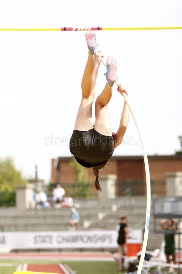 Pole Vault. Female athlete competing in the pole vault at a track and field event royalty free stock photo