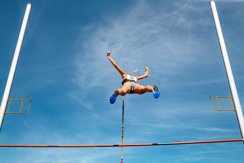 Pole vault woman athlete knocks bar. To fly background blue sky royalty free stock photography