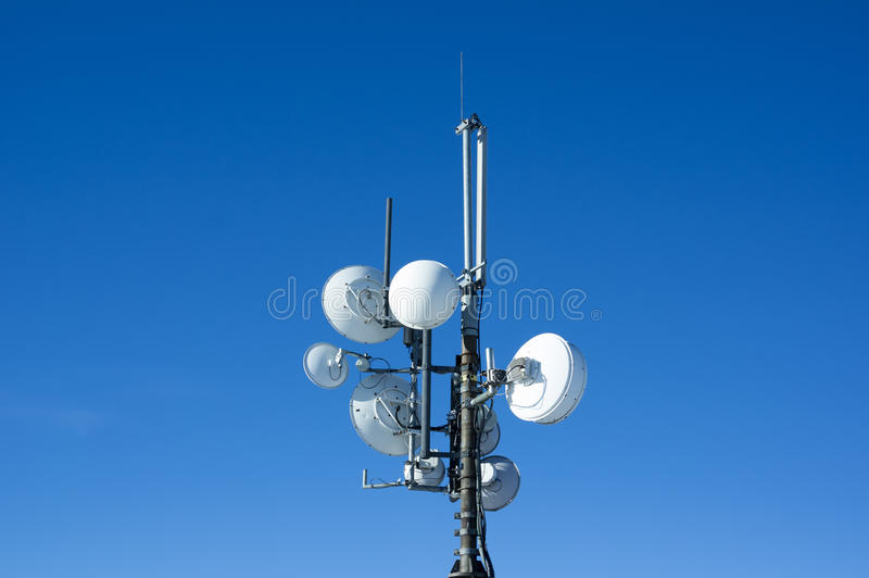 Pole with white satellites and antennas. Devices for provision, transmission and distribution of signal. Bright blue clear sky as background and copy space royalty free stock photos