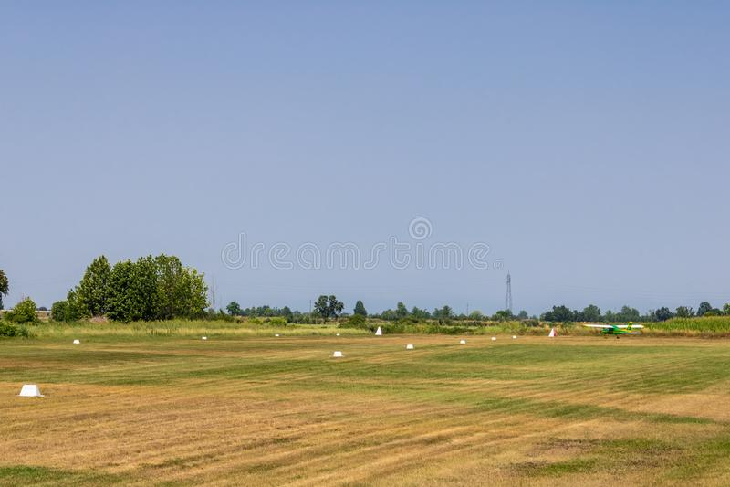 Pole z pasem startowym i małym samolotem, trawy pola pas startowy - wizerunek zdjęcia royalty free