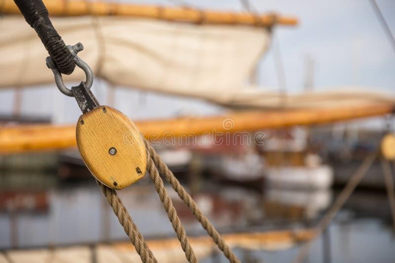 Polea para las velas y las cuerdas hechas de la madera en un barco de vela viejo, con la vela y otros barcos desenfocado en el fo imagen de archivo libre de regalías