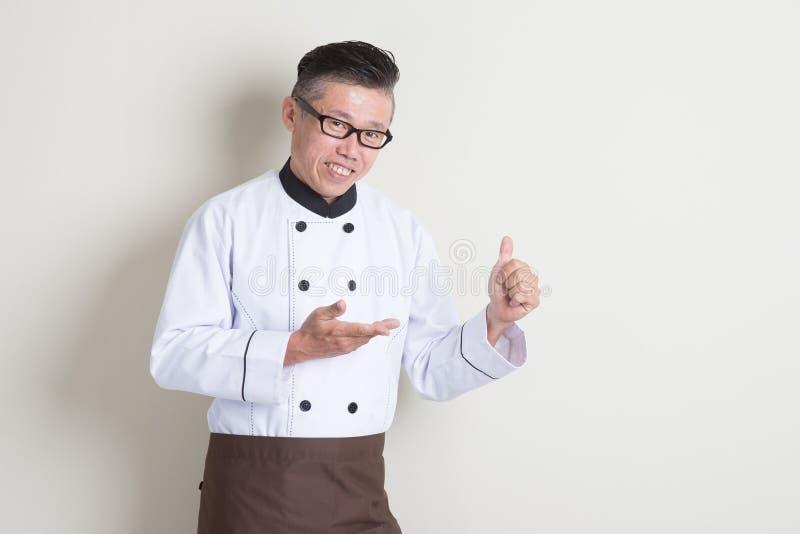 Polegar chinês asiático maduro do cozinheiro chefe acima imagem de stock royalty free