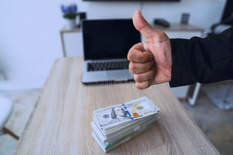 Polegar da exibição da mão do homem acima - como o sinal com muitos dinheiro no fundo, homens de negócios que trabalham ativament fotos de stock royalty free