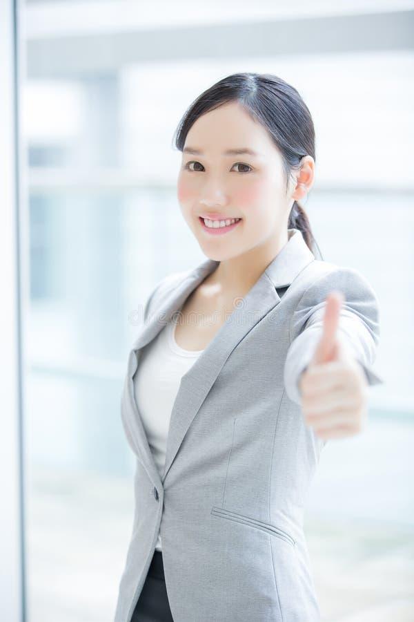 Polegar da mostra da mulher de negócio acima imagem de stock