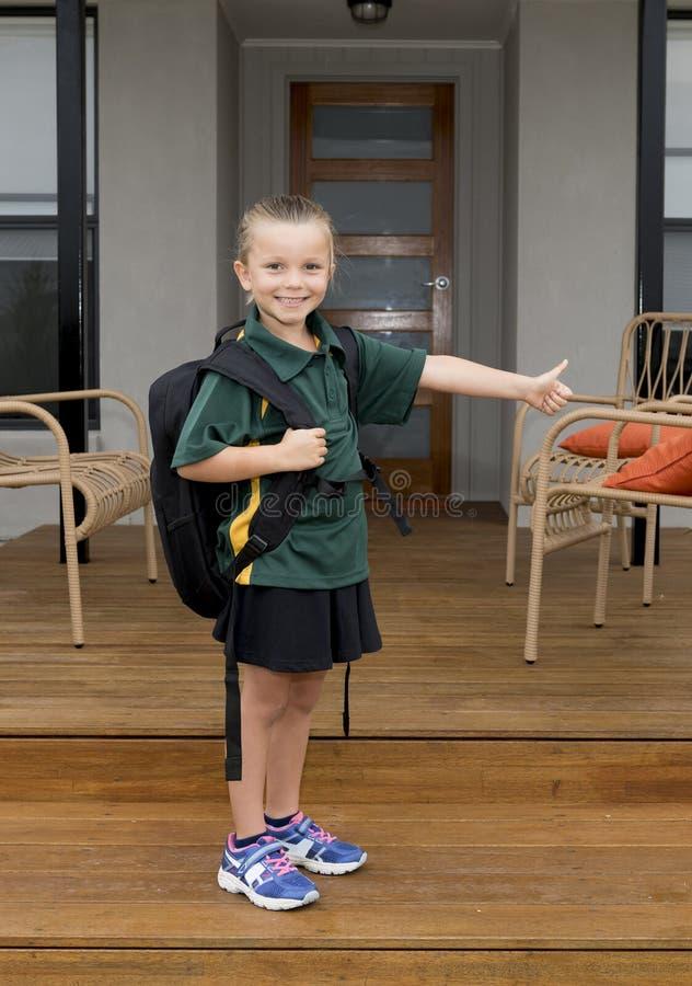 Polegar de doação feliz de sorriso da criança fêmea que leva acima o uniforme vestindo do estudante da trouxa da escola na estuda imagem de stock