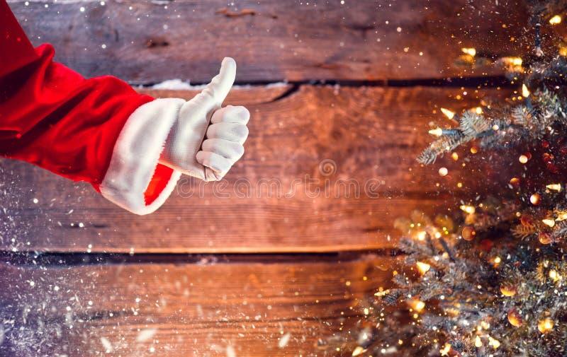Polegar de Santa Claus acima do gesto sobre o fundo de madeira do Natal fotografia de stock royalty free