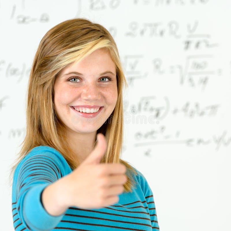 Polegar de sorriso da menina do estudante acima da placa da matemática imagem de stock royalty free