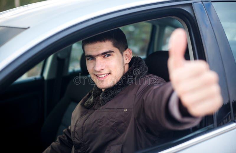 Polegar de sorriso novo do motorista acima em um carro imagem de stock royalty free