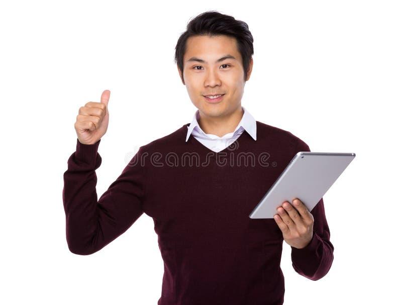 Polegar novo do homem de negócios acima do sinal com tablet pc foto de stock