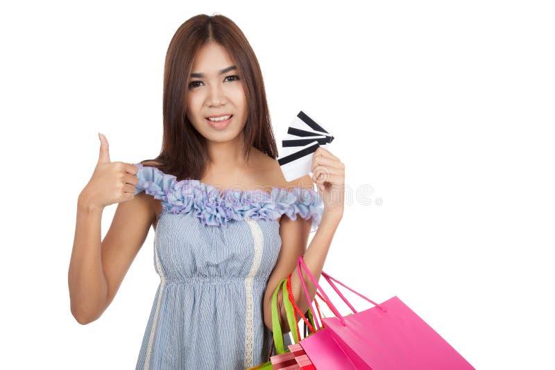 Polegares asiáticos bonitos da mulher acima com muitos cartões de crédito fotografia de stock