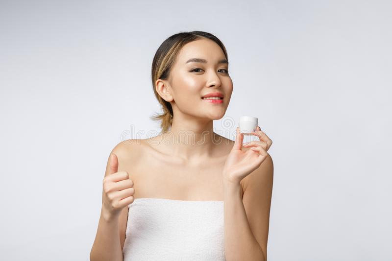 Polegares asiáticos da mulher da beleza acima para o bom produto facial Isolado no fundo branco Beleza e conceito da forma foto de stock royalty free