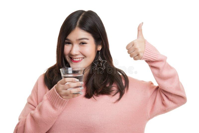 Polegares asiáticos novos da mulher acima com um vidro da água potável imagens de stock