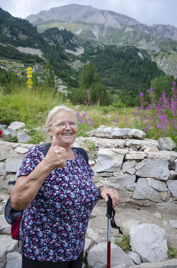 Polegares da senhora idosa acima para a caminhada da montanha fotos de stock