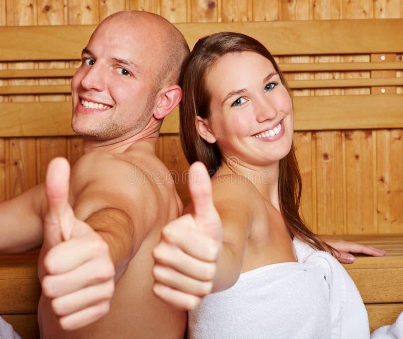Polegares da terra arrendada dos pares acima na sauna fotografia de stock royalty free