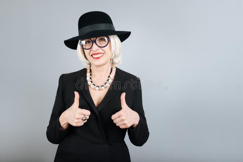 Polegares de aumentação de sorriso felizes da mulher superior imagens de stock