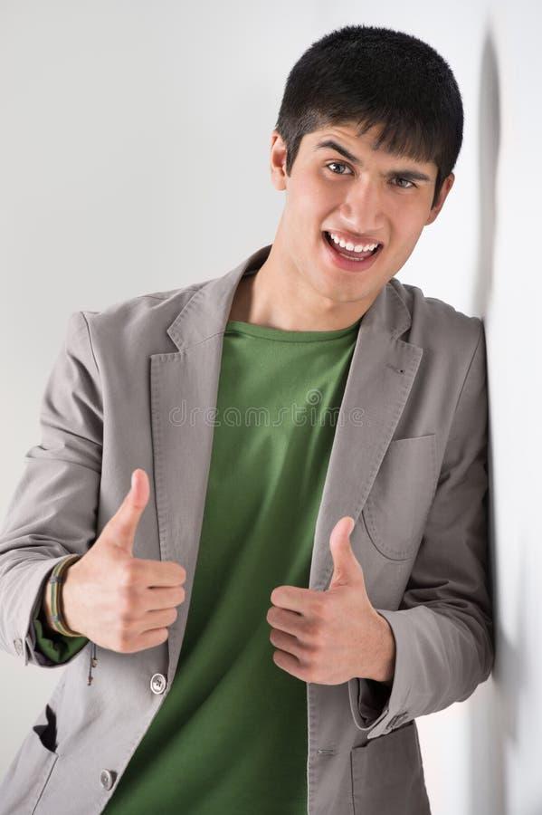 Polegares de sorriso felizes do homem novo acima fotos de stock