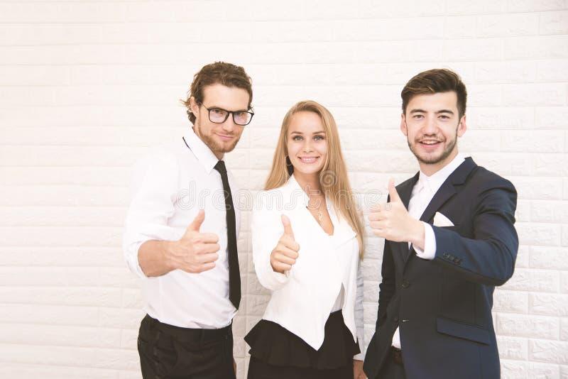 Polegares dos trabalhadores da equipe acima para o sucesso no negócio na frente da parede no café, o conceito do negócio e do suc foto de stock