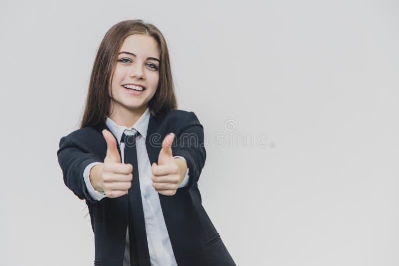 Polegares fêmeas dos gestos de mão acima A menina do negócio está sorrindo amplamente e compartilha de emoções positivas foto de stock