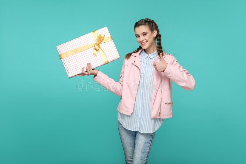 Polegares felizes acima da menina bonita no estilo ocasional e no revestimento cor-de-rosa, fotos de stock